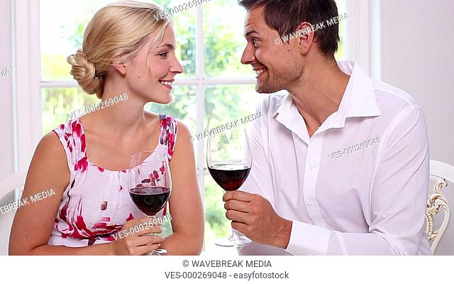 Happy young couple drinking red wine together