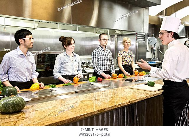 A Caucasian male chef teaching a cooking class for a mixed race grope of students in a commercial kitchen