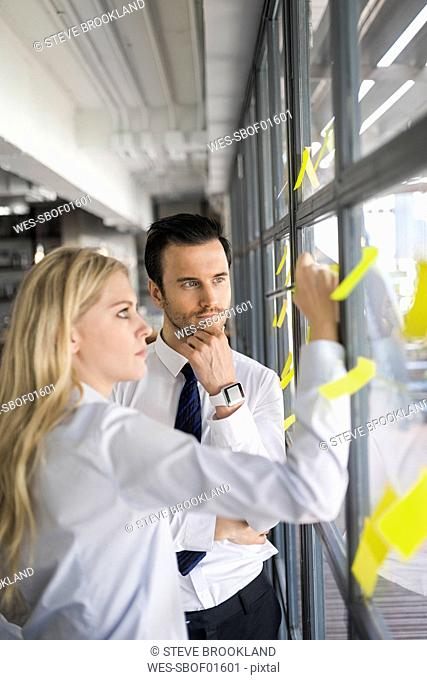 Colleagues writing on yellow post-its on window in office