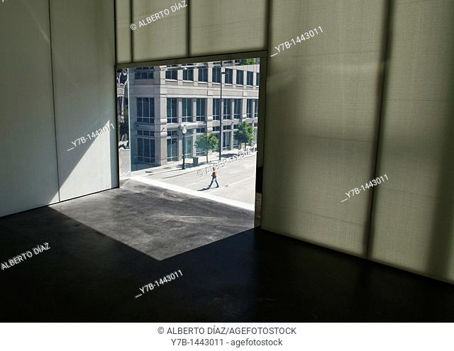 Hole in the window where the pedestrian is crossing an empty street in Denver