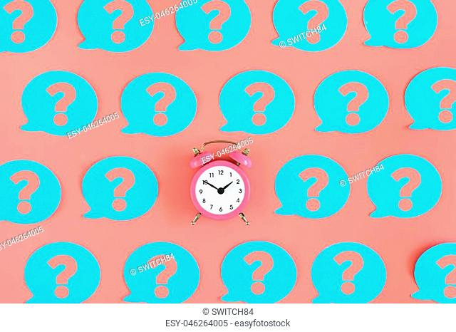 Many pink stickers with question marks are on the pink background. In the center is a small pink alarm clock. Concept, a matter of time