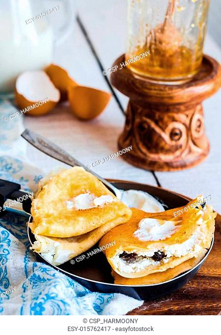 sweet pancakes with cottage cheese, prunes, honey in a frying p