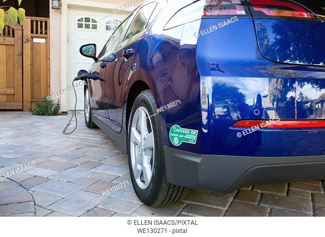 Plug-in electric car with carpool sticker parked in driveway, with connector plugged in and charging at home