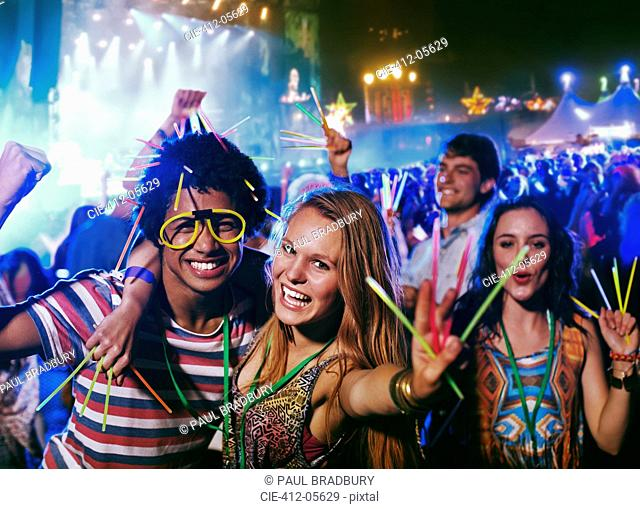 Portrait of friends with glow sticks at music festival