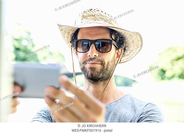Man wearing straw hat and sunglasses taking a selfie