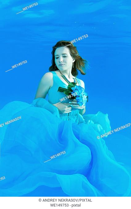 Young beautiful woman in a pale blue dress with a bouquet of flowers posing under water