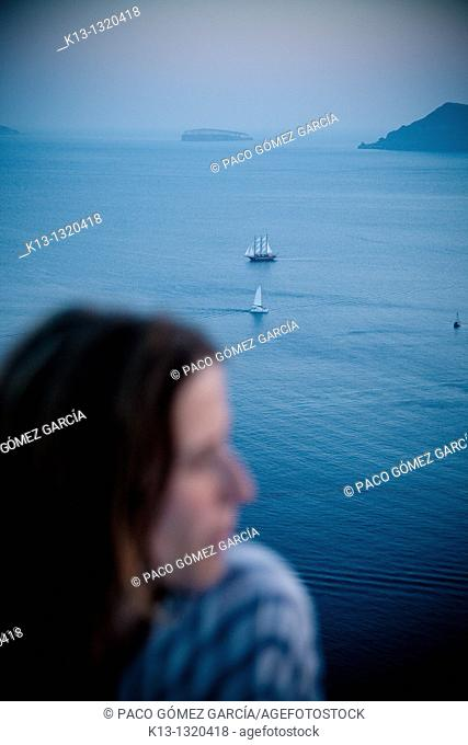 Woman and sailboat in Oia  Santorini  Cyclades Islands  Greece
