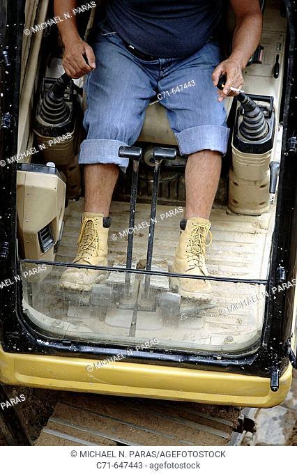 Heavy construction equipment operator working controls