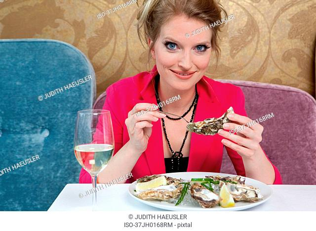 Woman having oysters in restaurant