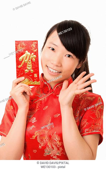 Beautiful Chinese woman holding a red envelope used to give a gift of money for the Chinese New Year
