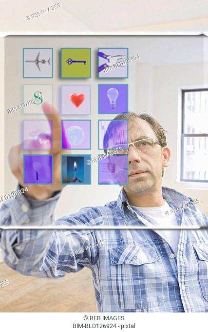 Hispanic man using mobile apps on virtual screen