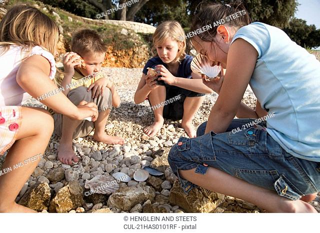 Children listening to shells at beach
