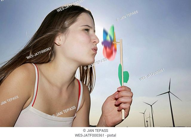 Germany, North Rhine-Westphalia, Neuss, Teenage girl with pinwheel in front of wind farm