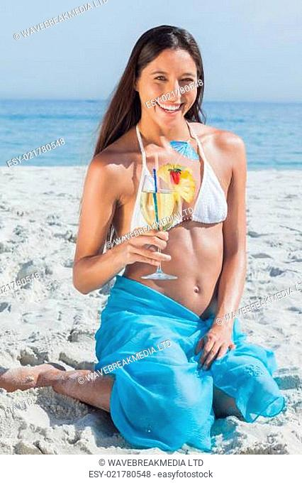 Smiling woman wearing sarong and holding cocktail