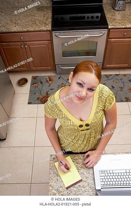 High angle view of a young woman writing on a notepad
