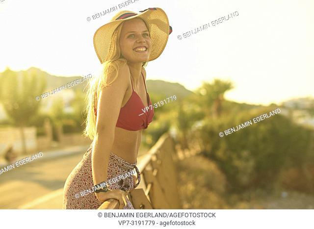 Woman leaning on handrailing next to beach, Stalida, Crete, Greece