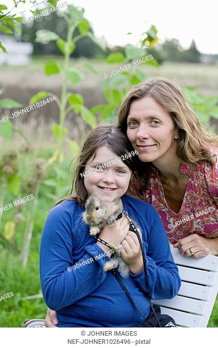 Sweden, Uppsala, portrait of mother and daughter with pet bunny