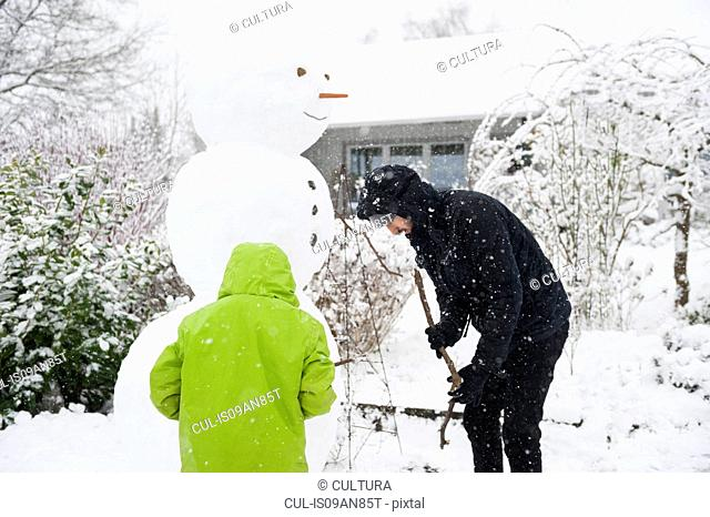Young man and boy building snowman together