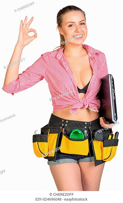 Woman in tool belt, with laptop under her armpit, showing okay sign, looking at camera, smiling. Woman in tool belt holding laptop under her armpit, smiling