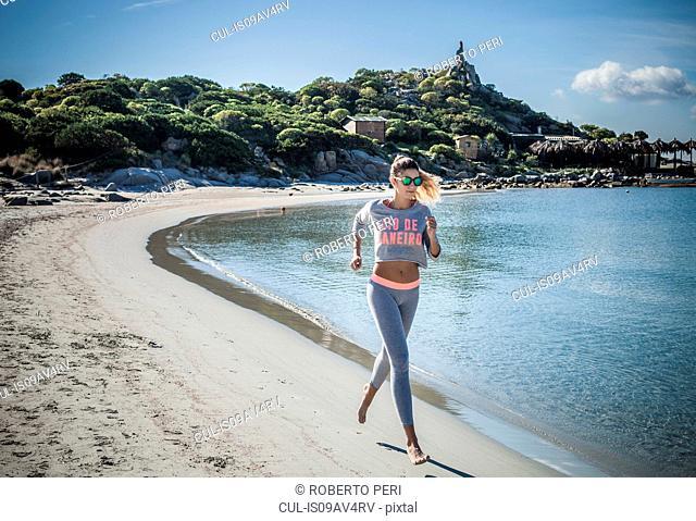 Female runner running along beach, Villasimius, Sardinia, Italy