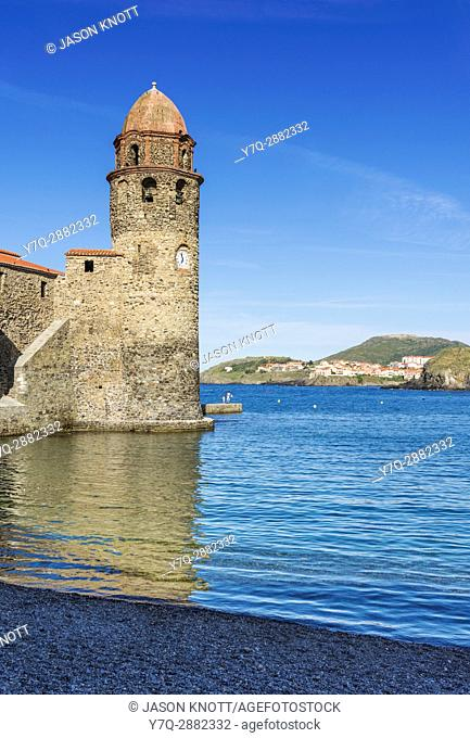 The bell tower of the Church of Notre Dame des Anges overlooking pebbley Boramar Beach, Collioure, Côte Vermeille, Céret, Pyrénées-Orientales, Occitanie, France