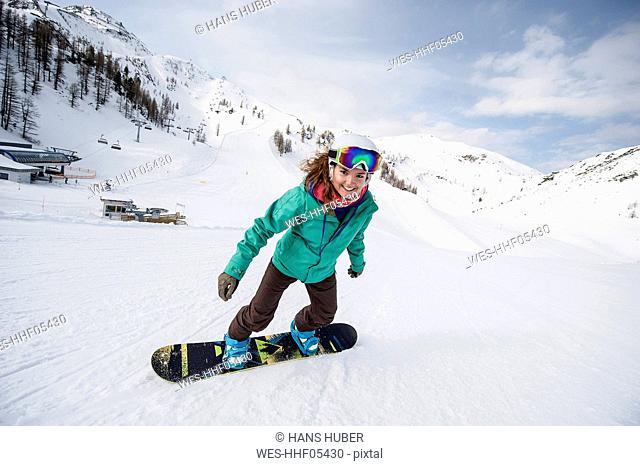 Austria, Altenmarkt-Zauchensee, smiling young woman riding snowboard