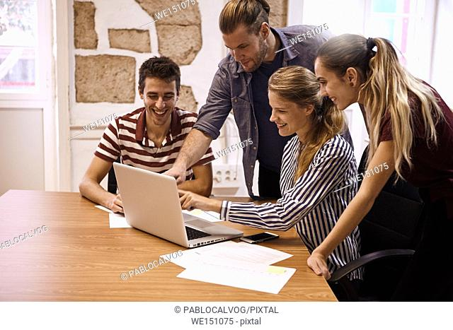 Young business team in a meeting with one male and one female both pointing at the laptop they are all sharing while everyone is smiling