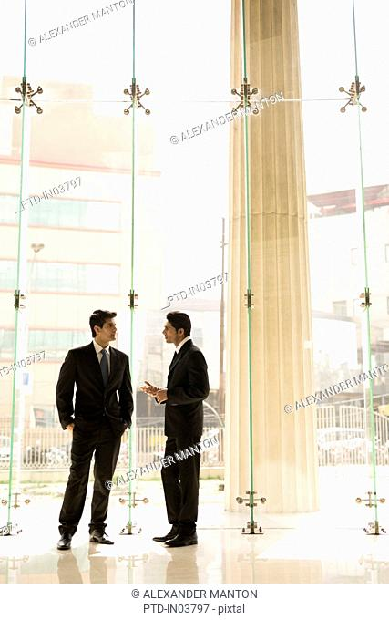 India, Two businessmen in suits talking in glass office lobby