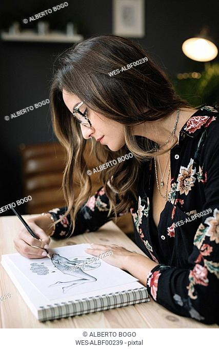 Portrait of woman drawing in sketch book at desk in tattoo studio