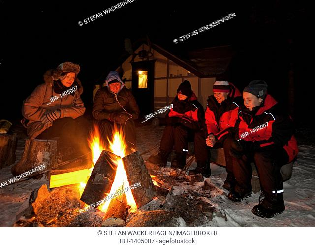 People sitting at a camp fire, bonfire, illuminated wall tent, cabin behind, Yukon Territory, Canada