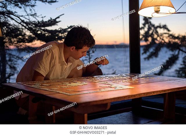 Teenage Boy Doing Jigsaw Puzzle at Lake House at Sunset