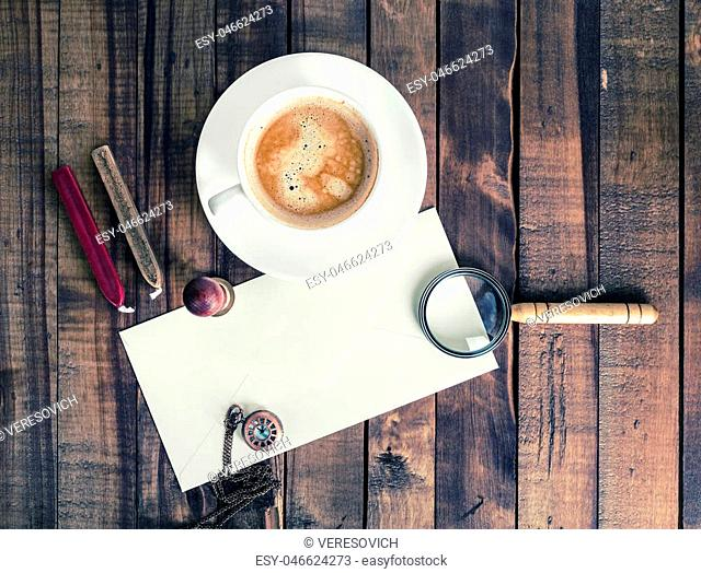 Blank envelope, magnifier, seal, stamp, clock and coffee cup on wood background. Postal accessories. Vintage stationery elements