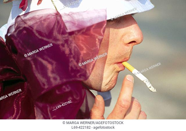 Man in a costume, smoking a cigarette