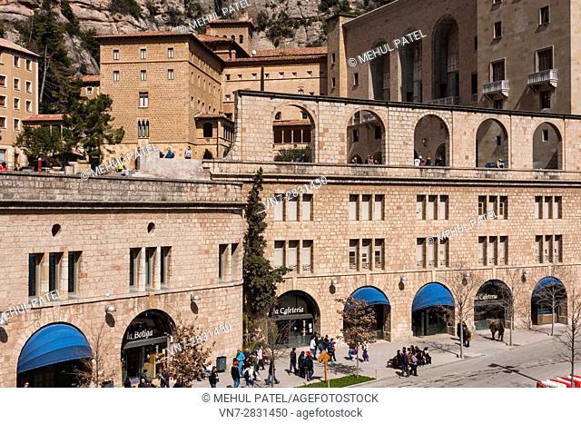 View of the Sanctuary of Benedictine abbey Santa Maria de Montserrat and the shop and cafeteria at street level on Plaça de a Creu