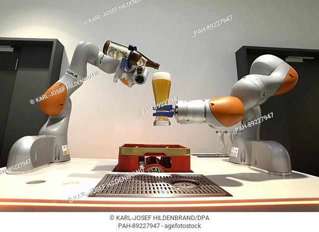 A Kuka robot pours beer into a glass at the 2016 balance sheet press conference of the industrial robot manufacturer held at the Kuka headquarters in Augsburg