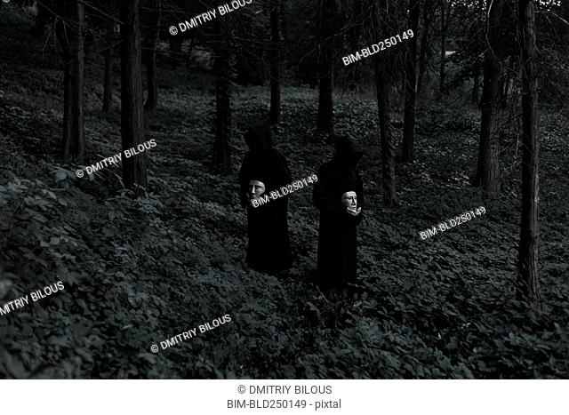 People wearing black robes and holding white masks in forest