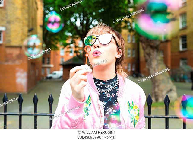 Retro styled young woman blowing bubbles