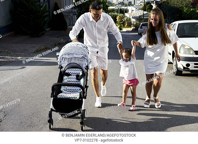 parents holding daughter on hands, walking on street, with buggy, parenthood, family, one child, candid, unposed. In holiday destination Chersonissos, Crete