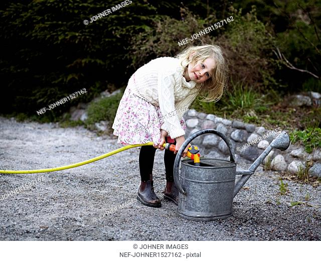 Girl filling watering can