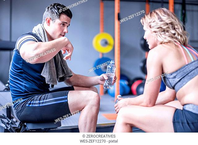Young man and woman having a refreshment break in gym