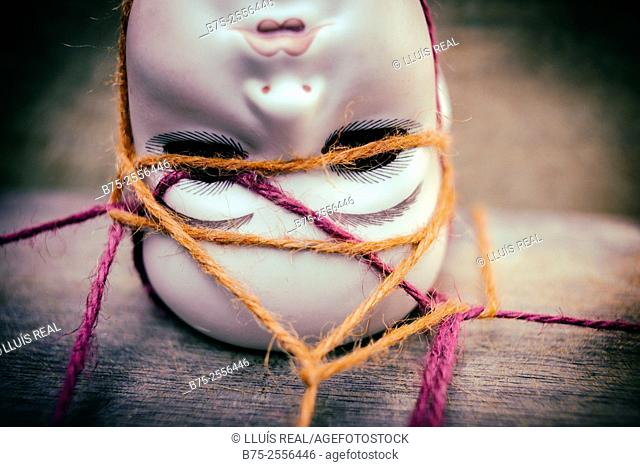 Head of antique porcelain doll tied with a red and orange rope