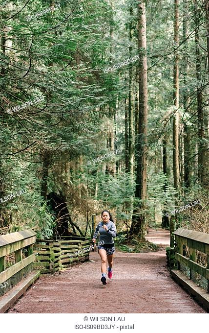 Woman running in forest, Vancouver, Canada