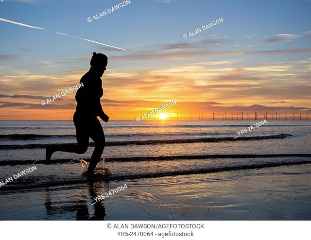 Woman running in sea at sunrise with Teesside Offshore Windfarm in distance. Seaton Carew beach, north east England, United Kingdom, Europe