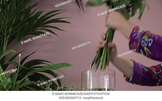 a florist manufactures a bouquet of roses