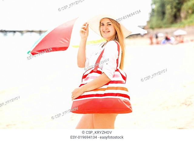 smiling woman in white hat with red bag posing in sea beach