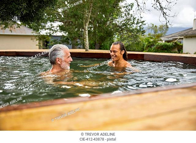 Father and son relaxing in hot tub