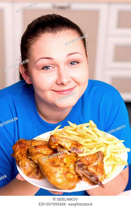 Overweight pretty woman desiring to eat big unhealthy plate with fried chiken and french fries