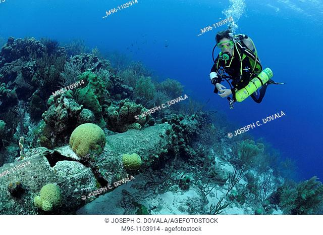 Deep diver slowly going back to surface looking at old mast, Bonaire Island, Netherlands Antilles, Caribbean