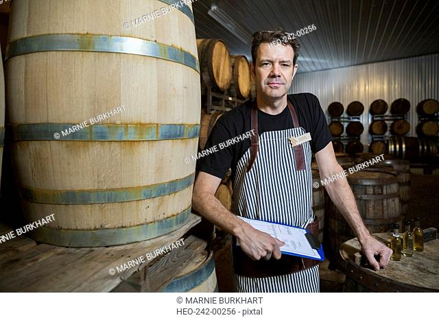Portrait confident distillery worker with clipboard in cellar