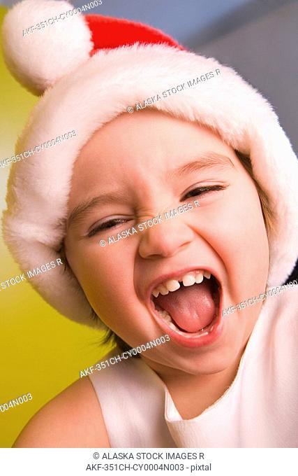Closeup portrait of young girl wearing Santa hat smiling winter Alaska